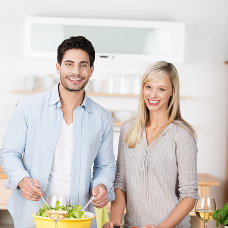 Attractive couple preparing a meal in the kitchen standing side by side at the counter as the husband tosses a green salad photo