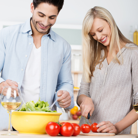 Happy couple standing smiling together in the kitchen as they work together as a team preparing a fresh salad photo