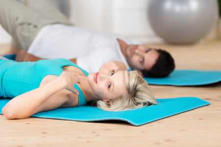Attractive woman working out at the gym with her husband as they lie on their backs on exercise mats on a wooden floor photo