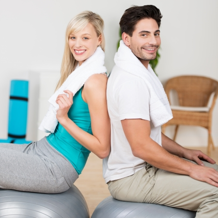 Young couple working out with pilates balls sitting back to back balancing on the top and turning to smile at the camera photo