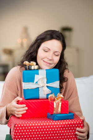 appreciating: Beautiful woman appreciating the joy of Christmas holding a pile of colourful Xmas gifts resting her chin on the top with a gentle smile of satisfaction