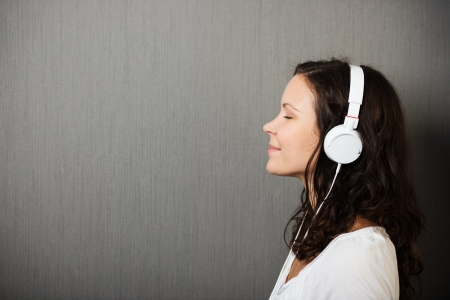 Serene young woman enjoying her music standing in profile listening to her headphones with a smile of pleasure, on a grey background with copyspace photo