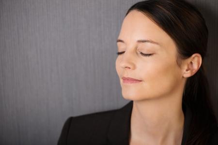 ojos cerrados: Joven y bella mujer serena con los ojos cerrados en la meditación de pie sobre un fondo gris con copyspace
