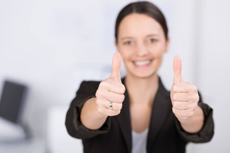 Smiling woman giving a thumbs up gesture with both hands as she communicates her enthusiasm, success and approval, focus to her thumbs Stock Photo
