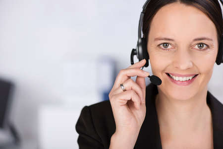 personal assistant: Friendly smiling receptionist, personal assistant or call centre operator , head and shoulders close up portrait with copyspace