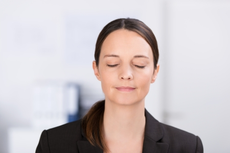 Head and shoulders portrait of a serene young professional woman standing meditating or thinking deeply with her eyes closed