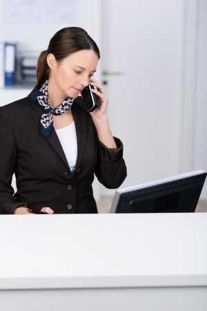 Smart beautiful young receptionist standing behind a counter at her computer taking a phone call from a client