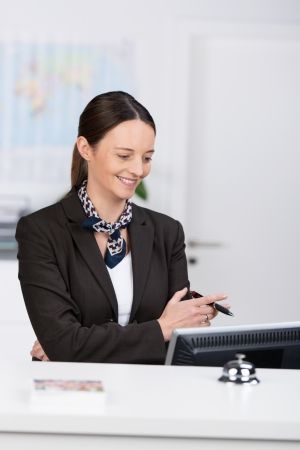at her desk: Stylish receptionist standing behind a hotel reception desk reading data on her computer with folded arms and a happy smile