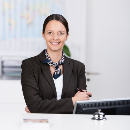 Welcoming confident friendly receptionist standing behind a hotel reception desk with her arms folded giving the camera a beautiful warm smile photo