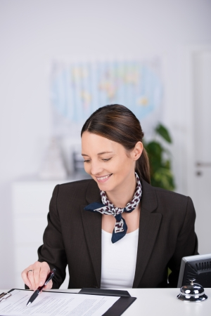 Smiling receptionist checking a clients booking standing at the reception desk pointing with her pen to an entry in a journal photo