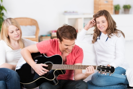 Teenage boy playing guitar music while sitting on a sofa in the living room flanked by two attractive smiling young female friends