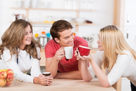 Three happy young college students having coffee together in the kitchen laugh and smile as they group around the wooden counter photo
