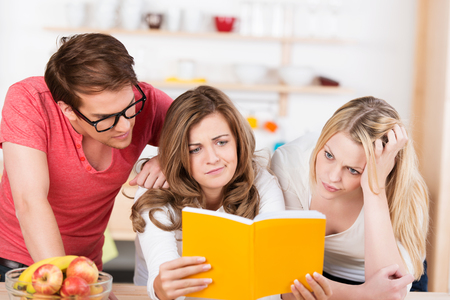 Three young friends trying to understand a book or recipe frowning in puzzlement as they read the text sitting at a wooden kitchen counter Stock Photo - 23909257