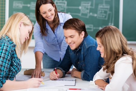 universities: Group effort in the classroom with a team of young teenage students studying on a project together around a table assisted by a smiling female teacher