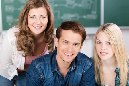 studygroup: Handsome young male college student sitting at a desk smiling at the camera flanked by two attractive young girls Stock Photo