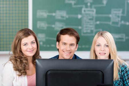 estudiantes adultos: Tres estudiantes adolescentes atractivas que trabajan en un equipo juntos en el aula sentado en una fila en un escritorio mirando por encima de la parte superior del monitor a la cámara