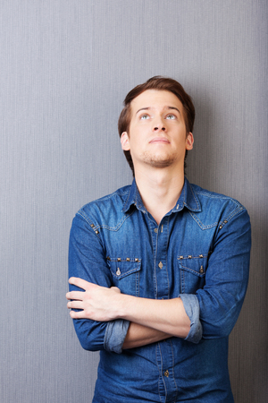 tilted: Young man standing thinking with his arms folded and head tilted back looking up into the air on a grey background