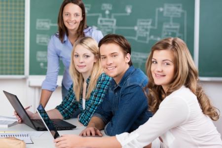 마지막에 서있는 여성 교사 자신의 노트북과 함께 테이블에 앉아 대학 교실에서 매력적인 십 대 학생의 웃는 그룹 스톡 콘텐츠