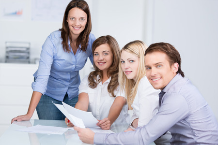 academy: Attractive middle-aged female teacher working on class notes with her students