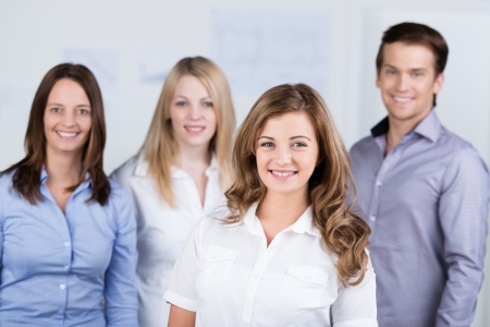 Smiling beautiful enthusiastic young businesswoman posing with her colleagues in the background at the office photo