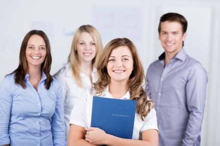 Happy succesvolle jonge vrouwelijke sollicitant die zich voor haar nieuwe collega's met een stralende glimlach geklemd een bestand met haar curriculum vitae Stockfoto
