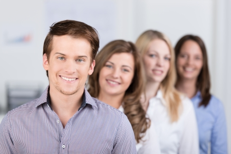 Successful young male business team leader or manager standing in front of his coworkers with a confident smile, shallow dof Stock Photo - 24458172
