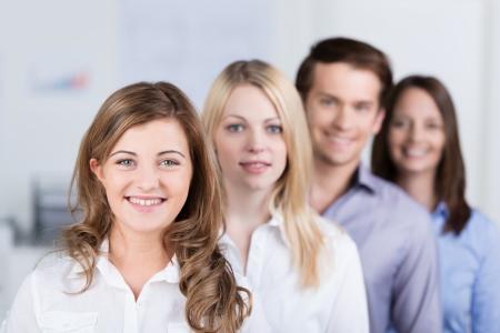 리더십 자질을 가진 정면에있는 아름 다운 여자에 초점을 카메라에 미소를 경사 행에 서 성공적인 젊은 비즈니스 팀 스톡 콘텐츠