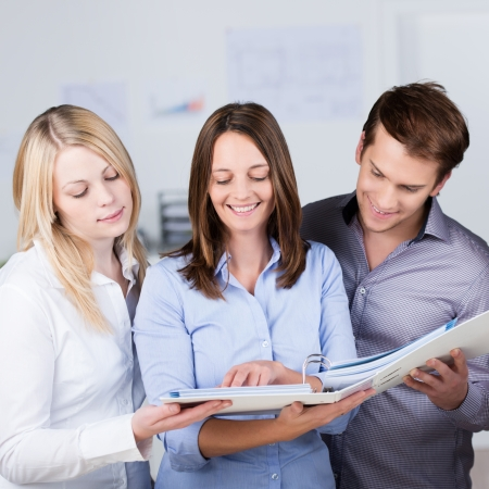 explain: Successful business partners consulting a file together held by the woman in the centre smiling happily as they see their project in print