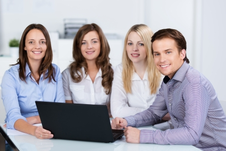Group of young business people sharing a laptop in the office sitting at a table together looking at information on the screen Stock Photo - 24458175