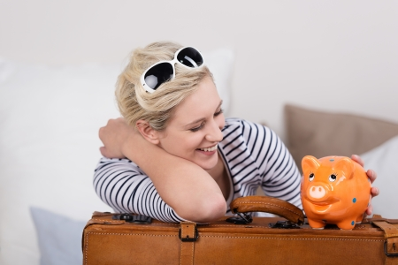 Trendy beautiful young female traveller with a piggy bank balanced on her suitcase and her sunglasses on her head smiling in satisfaction that her savings with pay for her travel and holidays photo