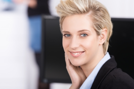 Attractive modern young businesswoman with a trendy blond hairstyle looking at the camera with a smile, close up head portrait photo