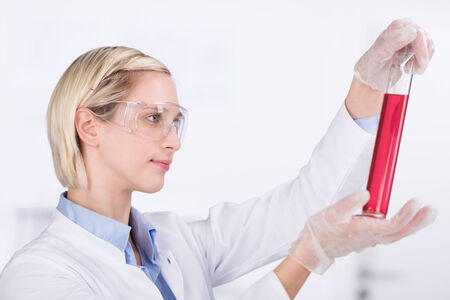 Female laboratory technician wearing protective goggles examining a red chemical solution in a glass cylinder while conducting tests photo