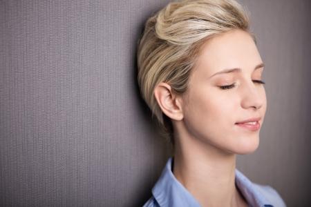 Donna pausa per la meditazione personale o introspezione in piedi con gli occhi chiusi e un'espressione serena contro uno sfondo grigio con copyspace