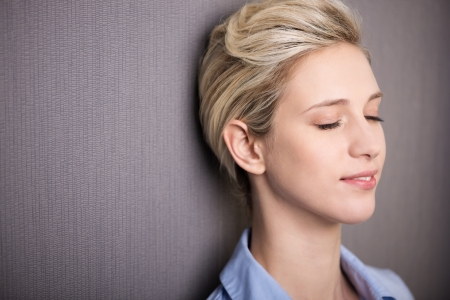 eyes closed: Woman pausing for personal meditation or introspection standing with her eyes closed and a serene expression against a grey background with copyspace Stock Photo