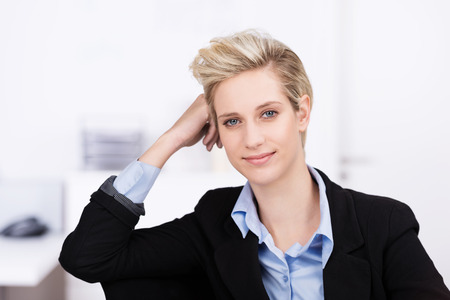 elbow chair: Attractive blond businesswoman taking a break at the office leaning her elbow on the back of her chair and resting her head as she smiles at the camera
