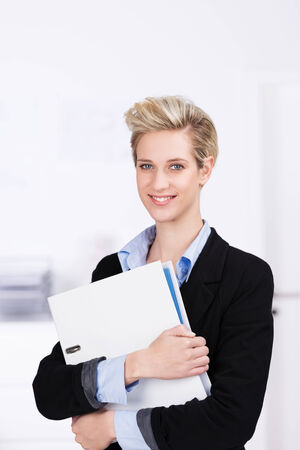 Confident young female business executive with a modern blond hairstyle and friendly smile clutching a large white binder photo