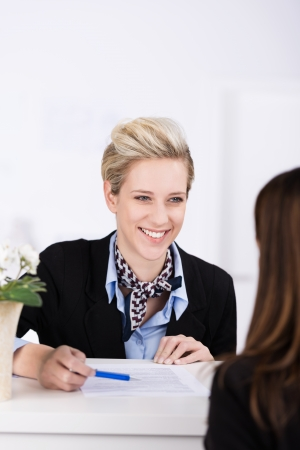checking in: Welcoming beautiful elegant young hotel receptionist smiling at a guest as she greets her at the reception desk for checking in Stock Photo
