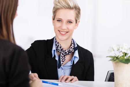 recepcionista: Hermosa recepcionista de pie detrás del mostrador asistir a un invitado a entrar en un hotel