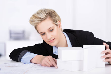 architect office: Business designer aligning white blocks as she sits at her desk assessing the best perspective for a product or advertisement Stock Photo