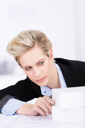 aligning: Beautiful blond businesswoman leaning sideways aligning two white blocks on her desk in the office