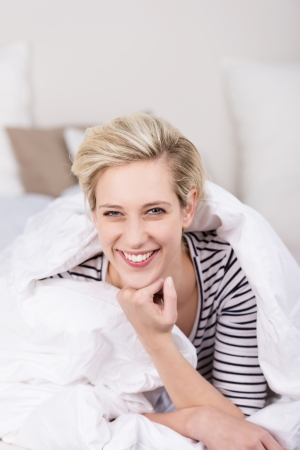 cuddled: Vivacious beautiful blond relaxing at home lying cuddled up in a duvet grinning happily at the camera