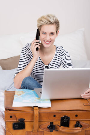 hotel booking: Woman booking her holidays over the internet sitting on her bed with her suitcase, map and laptop finalising the booking over her mobile phone