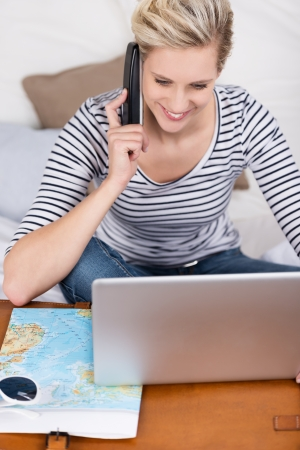 Excited woman planning her annual vacation over the internet smiling as she uses the mobile phone to place the booking photo
