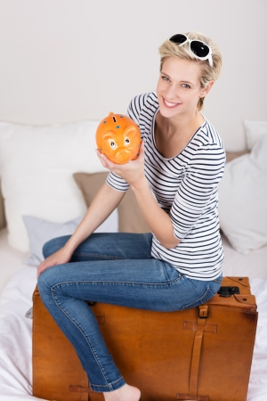 Elated trendy l young blond woman with her piggy bank sitting on her suitcase grinning at the camera with satisfaction as she plans to fund her travels from her savings Stock Photo - 24458325