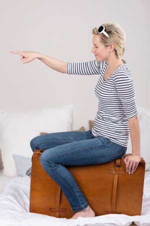 Playful woman choosing her travel destination sitting on her suitcase with her eyes closed pointing with her finger, side view Stock Photo - 24458367