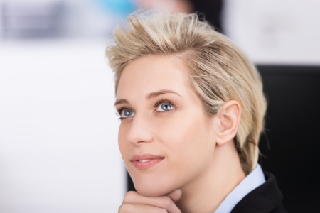 Beautiful young blond woman lost in thought sitting with her chin on her hand staring up into the air with a contemplative expression Stock Photo - 24458369