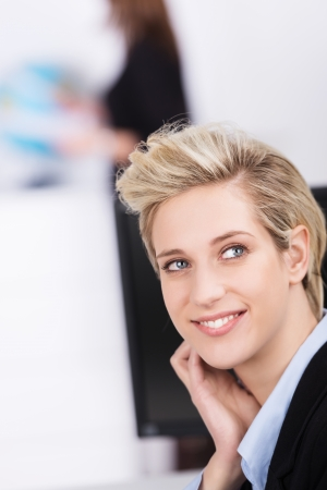 Beautiful young businesswoman with a modern blond hairstyle sitting in the office thinking or watching something with a happy smile on her face as she looks upwards Stock Photo - 24458371
