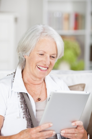 mujeres mayores: Mujer mayor sentada en su sala de estar leyendo un libro electr�nico en un tablet que sonr�e feliz como ella disfruta de la historia