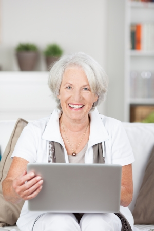 woman sitting with laptop: Happy senior lady using a laptop computer sitting on a couch in her living room with the notebook balanced on her knees as she surfs the internet