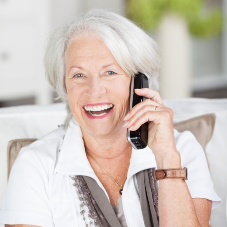 toothy smile: Vivacious attractive grey haired senior woman chatting on her mobile laughing as she shares a joke with the caller
